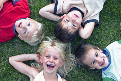 Children lying on grass in a circle